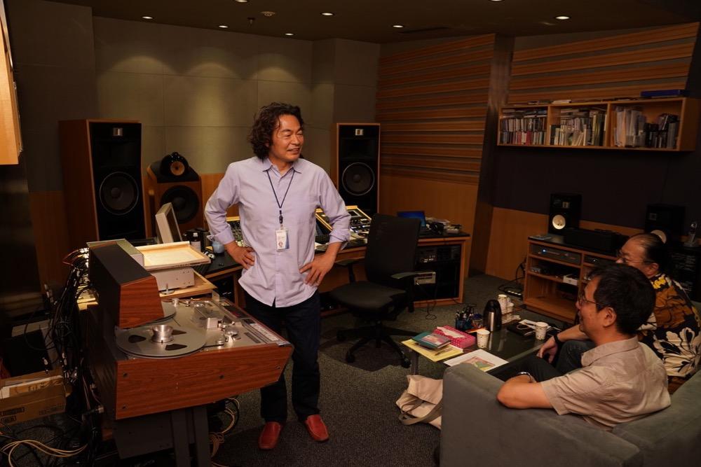 画像: これは2018年7月に行なわれたマスタリングの様子。ソニー・ミュージックスタジオで作業が行なわれた。エンジニアの鈴木浩二さんと音づくりの方向性について話し合う二人のスーパーバイザー