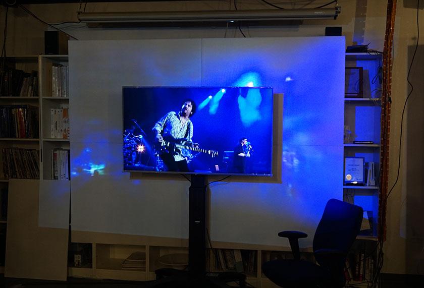 画像: 中央のライブ映像を元に、DCGANシステムが作り出した周辺視野映像を補完して上映。これにより、周囲の余計な情報が気にならなくなる効果が期待できる