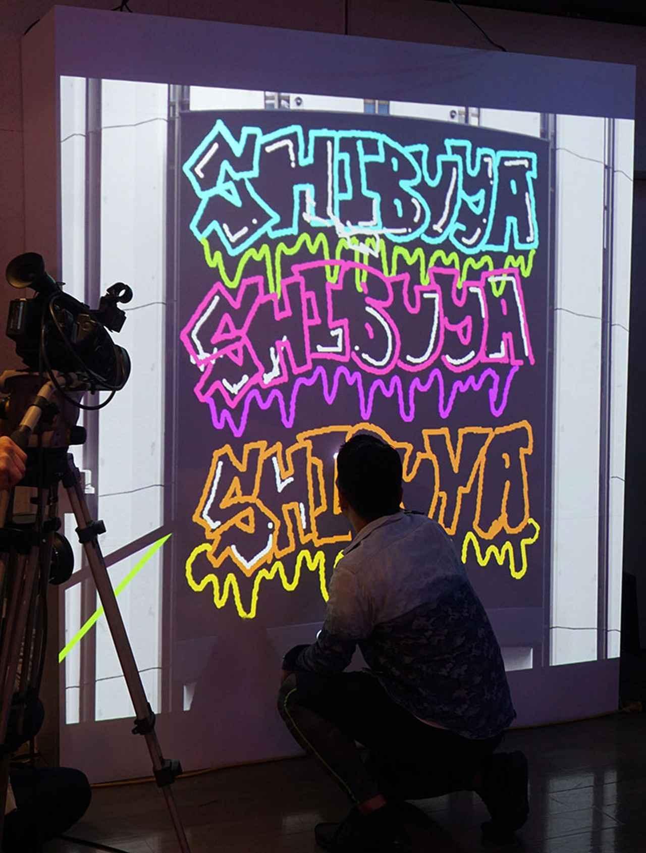画像: 会場でDoodle Penを使ってイラストを仕上げるNumber-D氏。下は映像を投写するプロジェクターで、当社レンズの下側に高速ビジョンセンサーが取り付けられている
