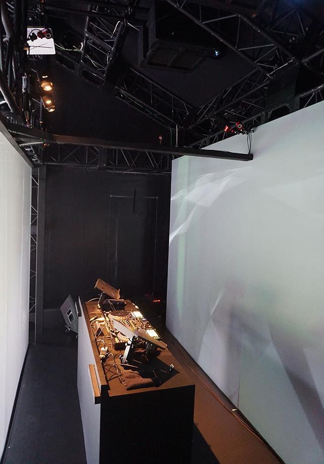 画像: インタラクティブキューブは客席側に透明スクリーン(上の写真)、その奥に反射型スクリーンが取り付けられており、DJはその間のスペース(左の写真)でパフォーマンスを披露する。彼らの動きをセンサーが感知して、スクリーンに様々な映像を上映するわけだ