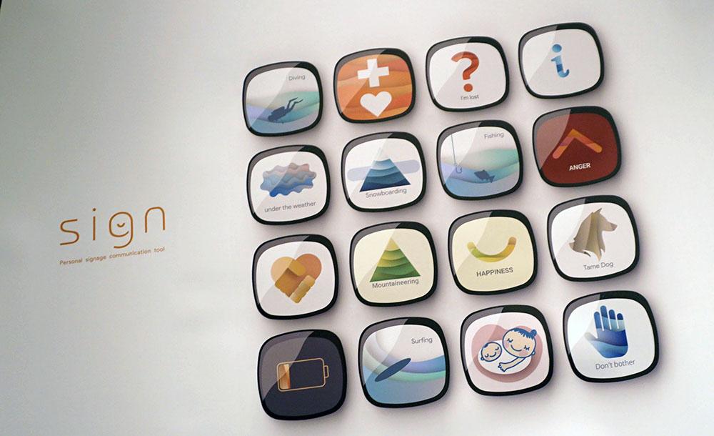 画像: 「個人が身につけ発信するサイネージの提案」 田中夢大君は、ウェアラブルデバイスを通じてユーザーが自身の情報を提案することで、快適なコミュニケーションの場を作ることを提案。5cm角ほどのデバイスには、あらかじめスマホアプリ等で選んでおいたマークを表示できる。共通の趣味がひと目でわかる他、マタニティマークのオン/オフなど場に応じた使い分けも簡単