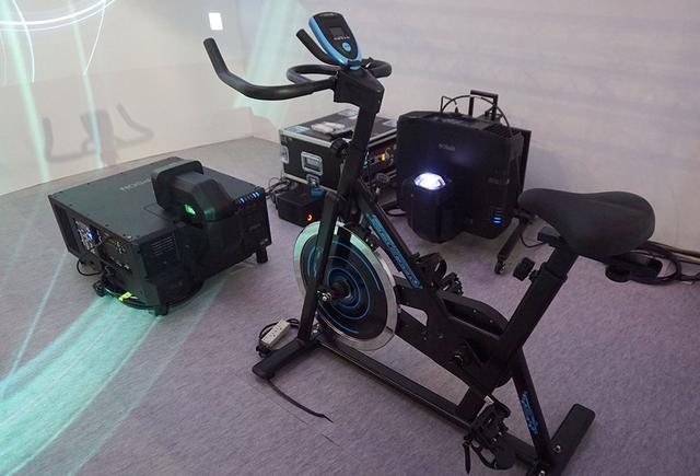画像: ペダルをこぐスピードを感知し、左のプロジェクターからの映像を切り替えている模様