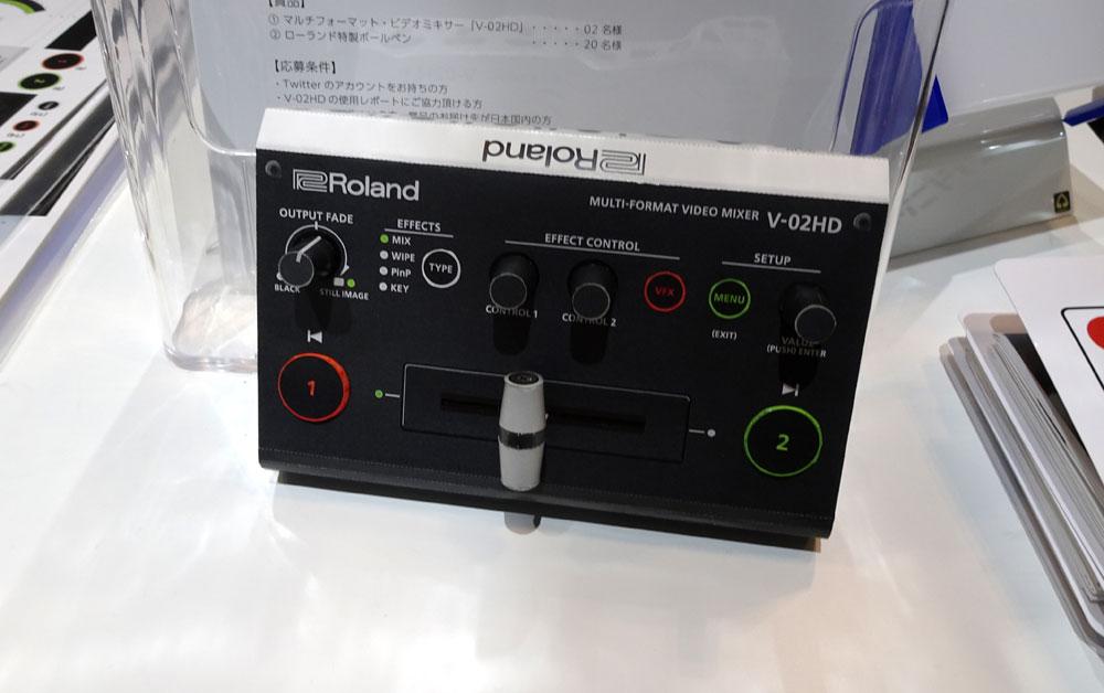 画像: ローランドブースの受付で配布されている「V-02HD」のペーパークラフト。上手に作ると、ホンモノが当たるチャンスも!