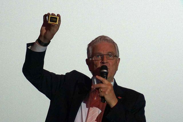 画像: 4KのDMDチップを手にプロジェクターの解説をするデヴィッド・キーリー氏
