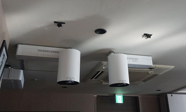 画像: 6Fラウンジの天井には赤外線センサ−(写真手間の小さな黒い四角)と、ホワイト仕上げのプロジェクターEV-100が取り付けられている