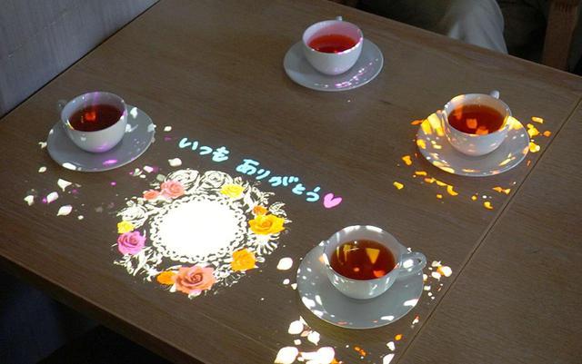 画像: 6Fラウンジのテーブルでは、提供された料理(あたたかいもの)を検知して映像が投写される。あらかじめ予約しておけば、写真のように手書きの文字を再生することも可能
