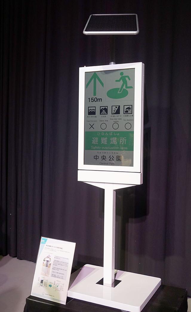 画像: スマートバス停のサンプル。液晶部分には時刻表や路線図を表示可能。必要に応じて多言語での説明等も準備できるそうだ。データの切り替えは無線経由で行なう。電力はバス停上部の太陽電池でまかなえる