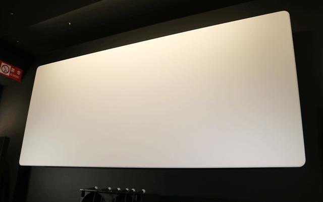 画像: スクリーンは剥き出しで設置。生地はオーエスの「サウンドマット」。サウンドホールのないタイプだが、細かく織込まれた生地を通して音が出てくる。スクリーンの後ろに、田口音響研究所の平面スピーカーが3基(LCR)設置されている