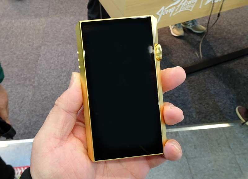 画像: Astell&kernブースでは、デジタルオーディオプレーヤー「SP1000M」の特別モデル「SP1000M GOLD」を参考展示。真鍮製のボディに金メッキを施したプレミアムなモデルだ。近日発売予定だという