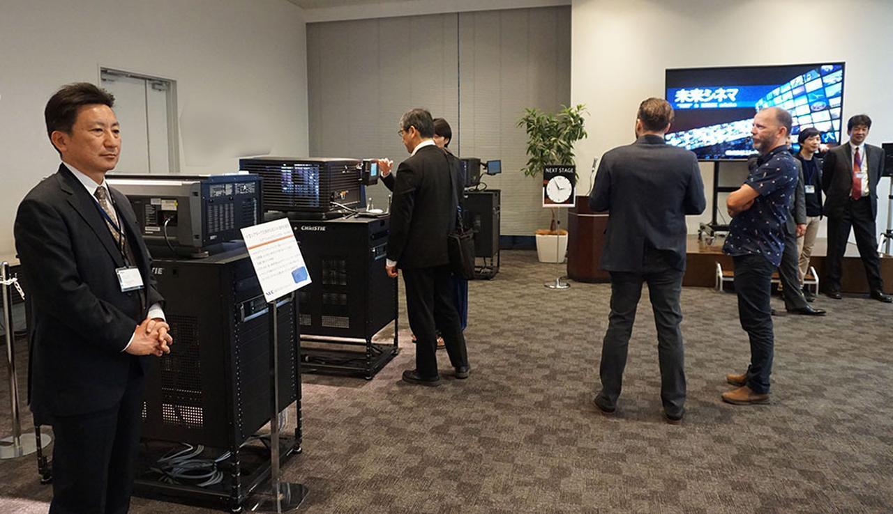 画像: 一台のサーバーからネットワーク経由で複数のプロジェクターに映画を配信する「未来シネマ」のデモ。会場では3台のプロジェクターで別々の作品を上映しており、音量調整などもアプリで操作していた。シネコンの上映環境を大きく変えそうな提案だ
