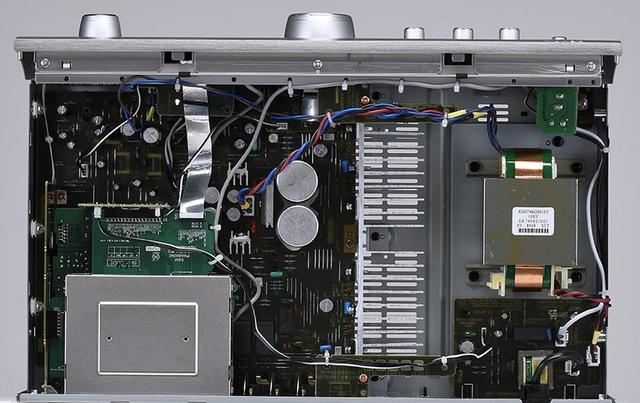 画像: ↑写真左上のボックスは放射ノイズを低減するためにシールドケースに覆われたデジタル入力基板が収まる。電源部(写真右側)にはPMA-800NE専用に開発されたカスタム仕様のコンデンサーが備わる。HC(High Current)トランジスターを用いた出力段は、中央のヒートシンクにマウントされている