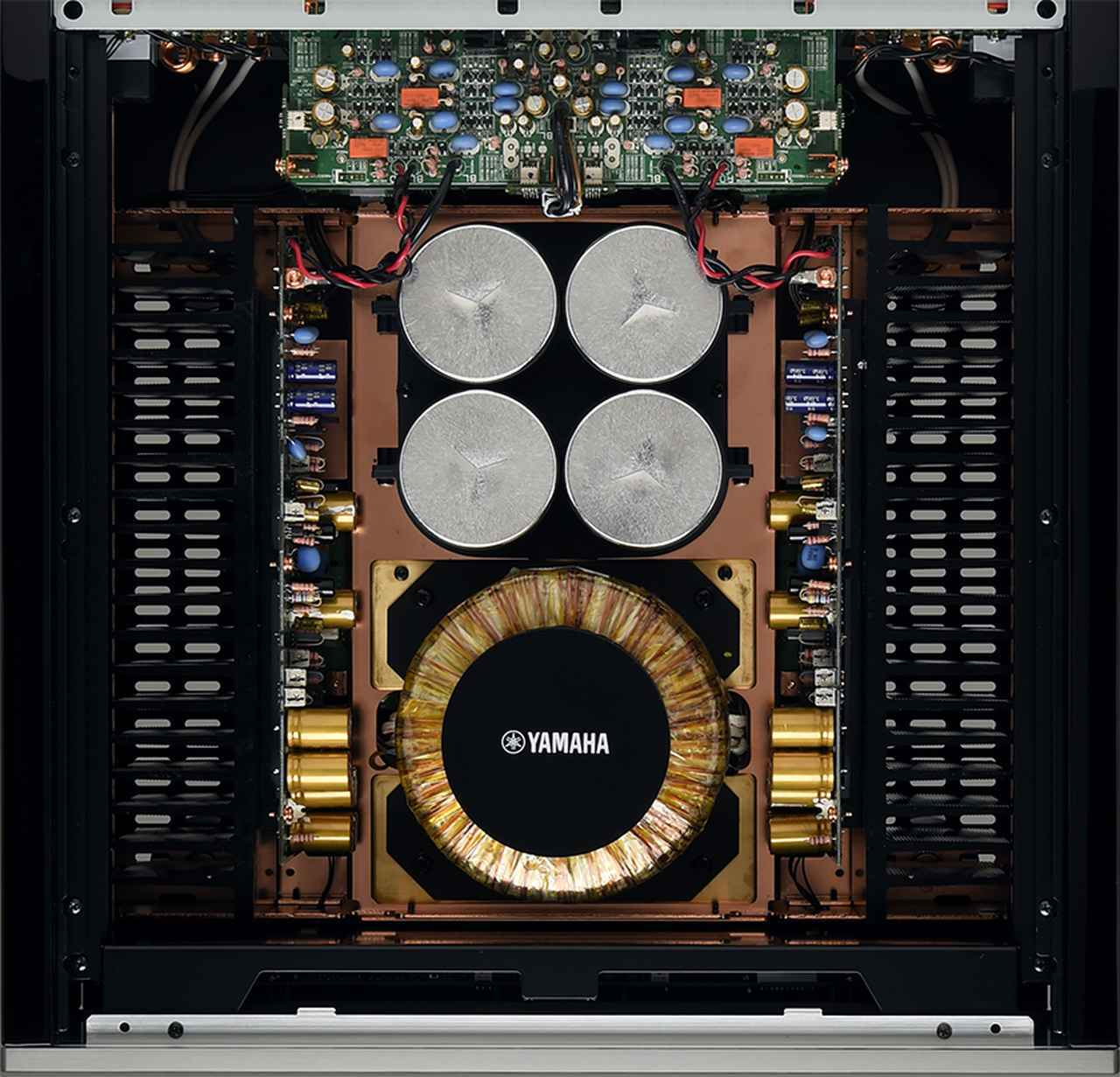 画像: ↑C-5000はフロント側に左右チャンネル別の大容量トロイダル電源トランス(各25VA)を用意。トランスとシャーシの間には3mm厚の真鍮ベースを挟み込む音質チューニングも施されている。ふたつのトランスの間にはこちらもチャンネル別の電源整流回路(上下2層)を搭載し、リア側の各チャンネル基板へと最短距離・左右等長での給電を実現している