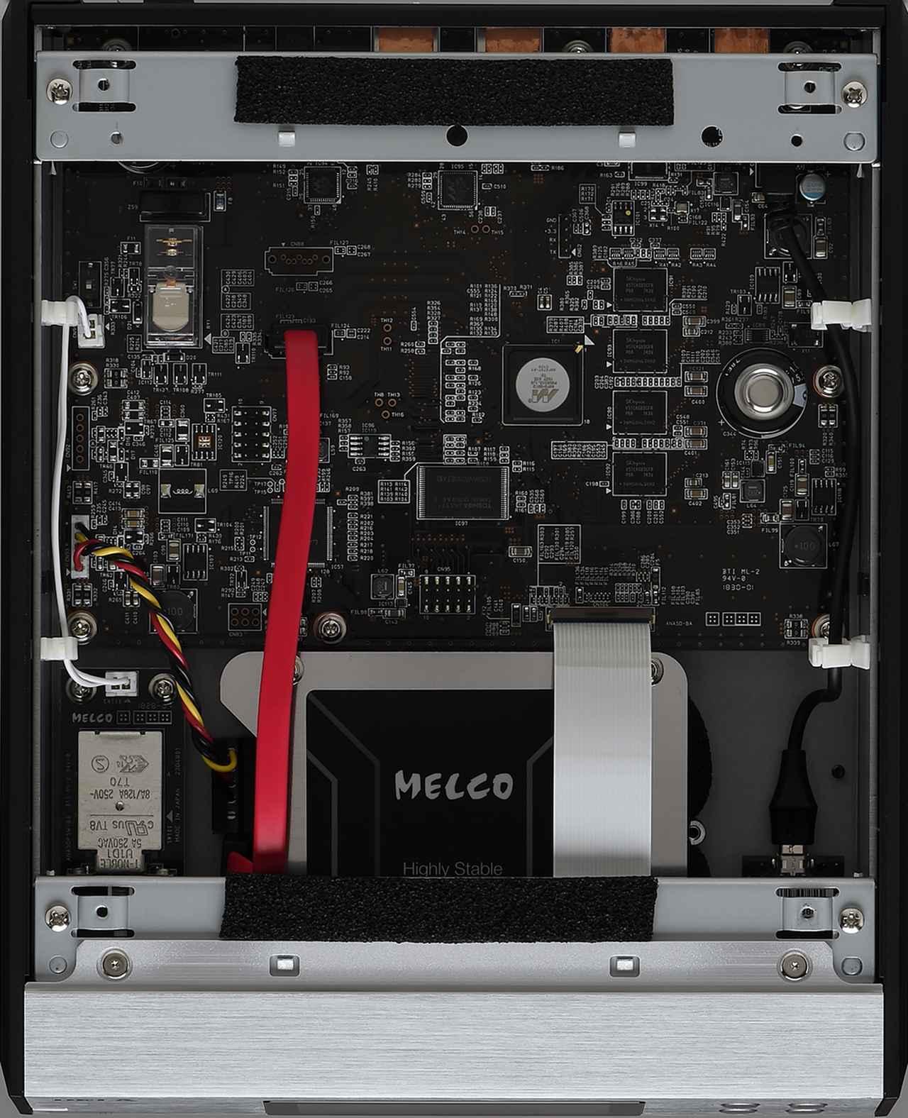 画像: 筐体前方のMELCO印の部分が3TバイトのHDDトレージ。HDD下部にステンレス鋼板を固定し、さらに制振素材を介してベースシャーシにリジッドな状態でマウント。HDD上部も吸音材を介して3mm厚ステンレス鋼板で覆い、万全の振動対策を施している。NDK(日本電波工業)製のC/N(搬送波対雑音比)の低い高性能パーツが用いられている