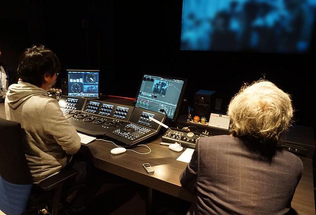 画像: グレーディング作業の様子(実際は別のスタジオで行われた)。木村大作撮影監督は山下さんの後ろのソファに座って、スクリーンの映像を見ながらどこを修正するか指示を出してくれたそうだ