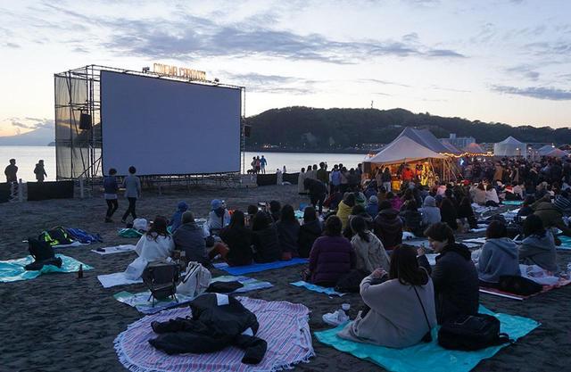 画像: 波打ち際にセットされた大型スクリーンに映画が上映される。日が沈む頃には夕焼けをバックに幻想的な風景が広がる