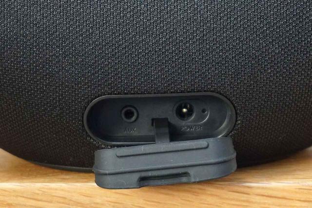 画像: 本体背面下部にACアダプターのコネクター(右)とアナログ音声入力(左)を備える。防水用カバー付きだ