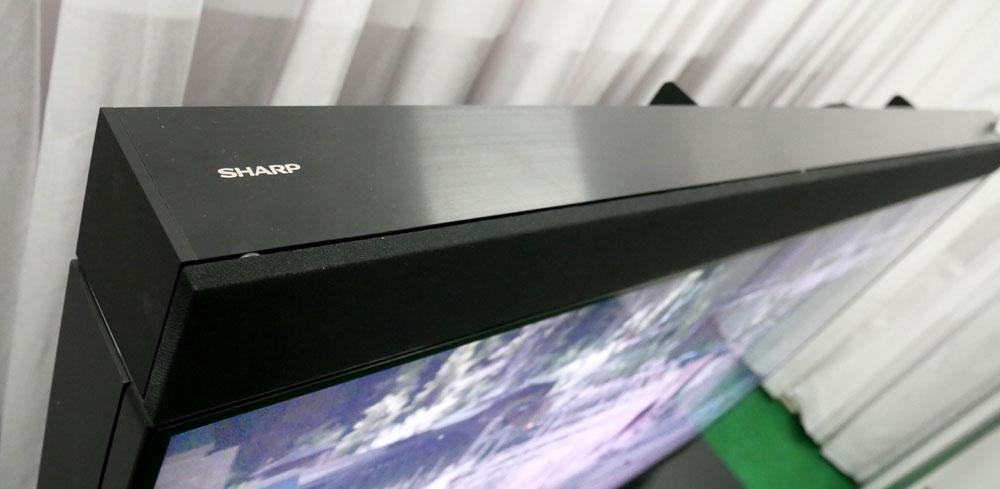 画像: ▲ディスプレイの上下にはサウンドバータイプのスピーカーを設置。一ユニットあたり25個のスピーカーを内蔵する