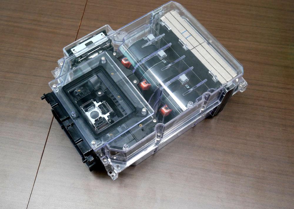 画像: 密閉化した光学ブロックの模型。中央に三つ並んでいる円柱形のものがファン。映像(光)は、左下に向かって投写される