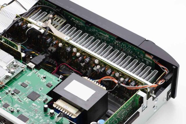 画像: 内部を開けて見ると、ヒートシンクに7ch分のディスクリートアンプ(ICのような集積回路ではなく、単体素子の組合せでつくられた回路)が取り付けられている。こうしたアンプとしてのこだわりから、マランツのNRシリーズは2chシステムのアンプとして使われる例も多いのだという