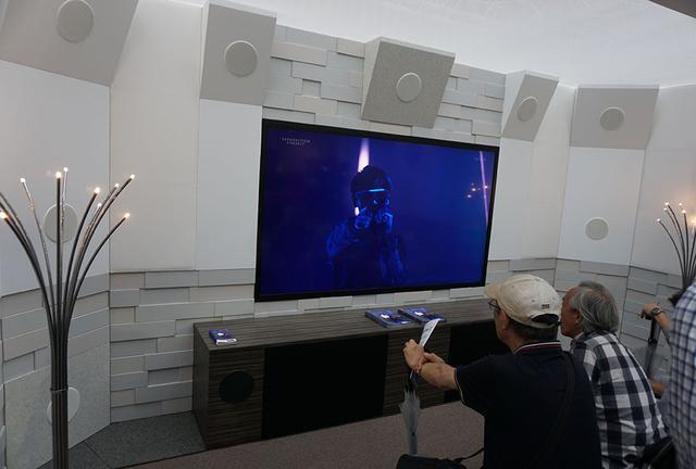 画像: 受付横の22.2ch体験コーナーには8Kディスプレイを中心にインウォールスピーカーがセットされている