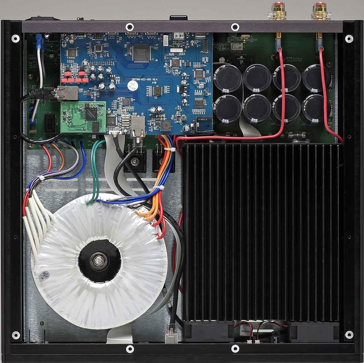 画像: 電源回路は、電力容量771VAの大型トロイダルコアトランスと総容量80,000μFの電解コンデンサーで構成。トランス横の大型のヒートシンクは、一定温度を超えるとフロントパネル側に設けた小型ファンで冷却を行なう。電力増幅回路はAクラスのアンバランス回路構成だ