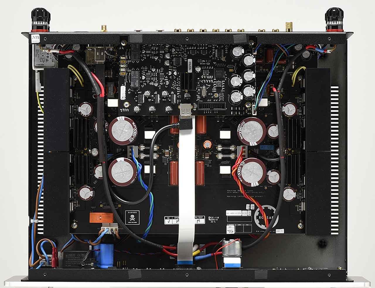画像: ↑左右対称を志向したプリメインアンプ内部。左右端に配されたヒートシンクに出力素子が載せられている。また、写真では見えないが100V専用としたトロイダルコアトランスは底面に備える