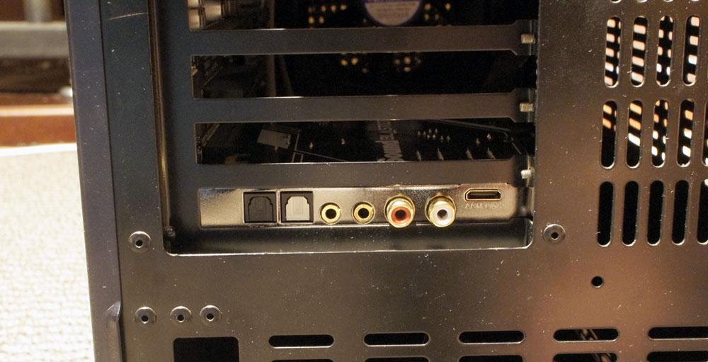 画像: パソコン背面から端子部を見たところ。左から光デジタル入力、光デジタル出力、サラウンド用出力端子×2(ステレオミニ)、フロント出力端子(RCA)、ACM用接続端子となる