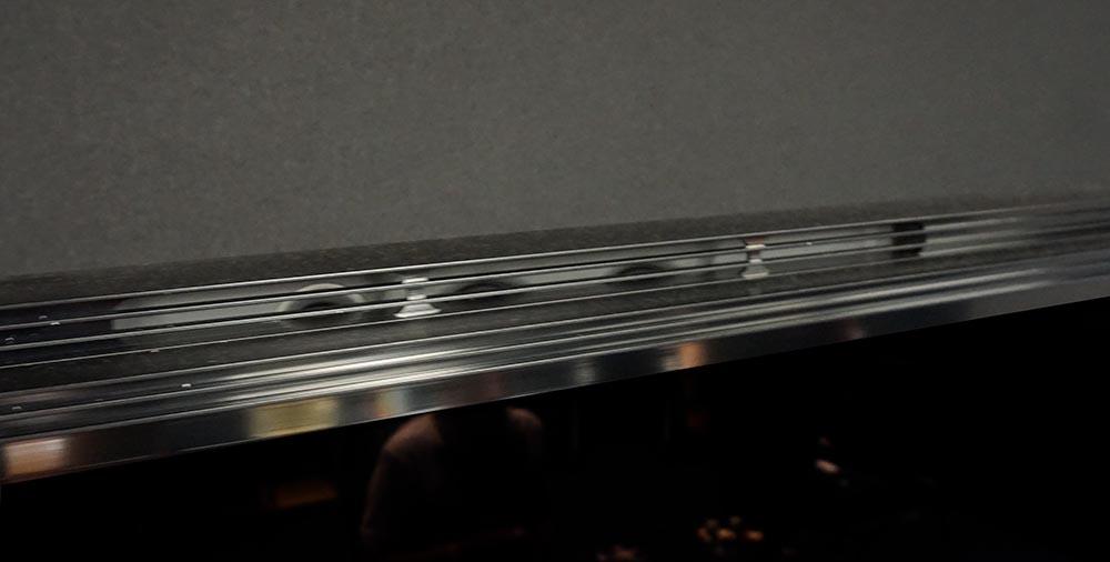 画像: Z9Gシリーズでは、本体上下のベゼル部 左右各2ヵ所、合計4基のスピーカーを搭載することで、映像と一致した音場再現を目指している。写真は上側の開口部で、奥に楕円型ユニットが取り付けられている。サブウーファーは85インチモデルは2基、98インチモデルはひとまわり大型ユニット1基を背面に搭載する