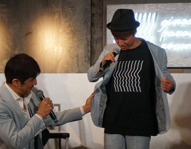 画像: トークショウでは、メンバー9人のシルエットをイメージしたオリジナルTシャツをNARGOさんが着用していた。会場B4Fで購入可能