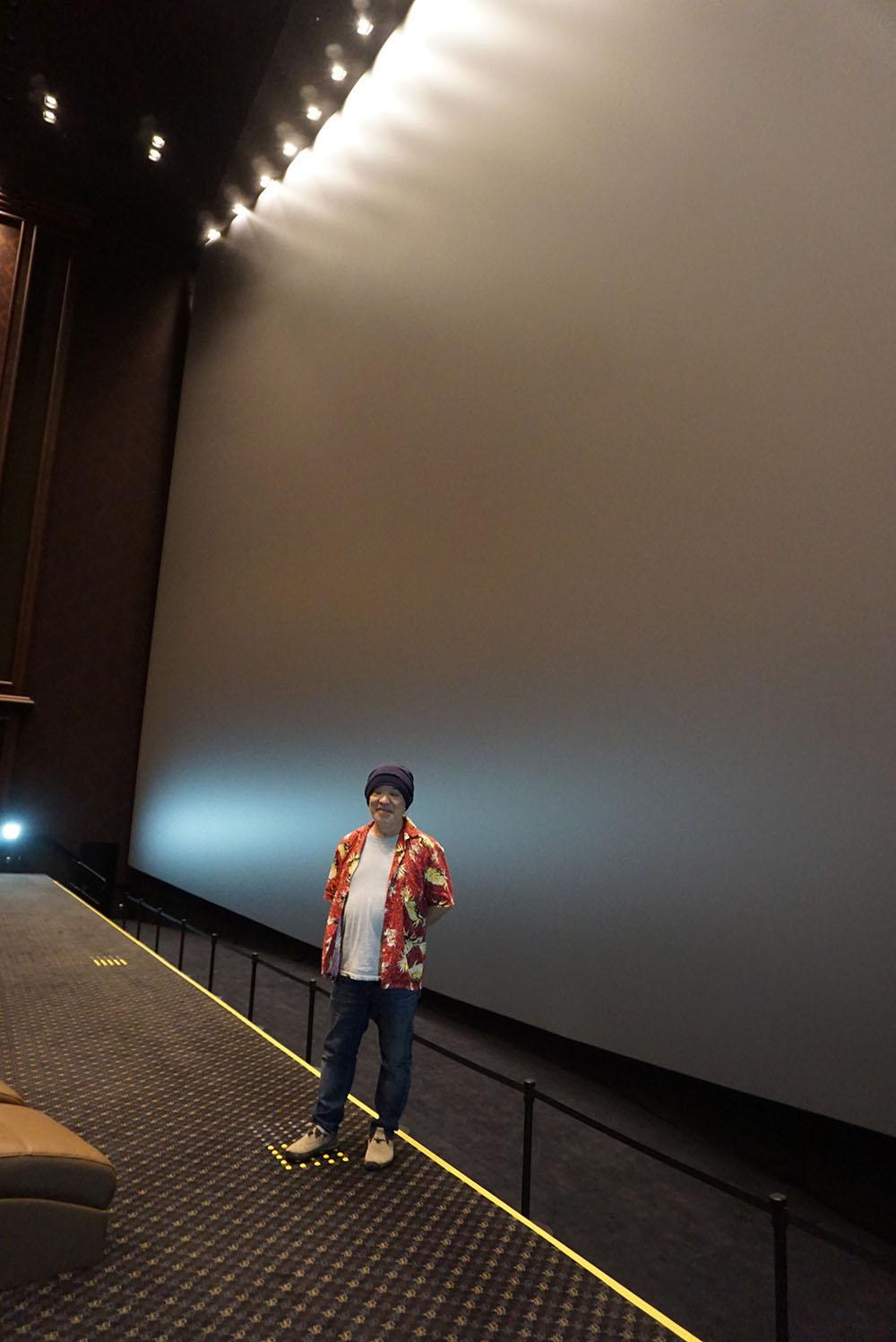 画像: スクリーン前に立つ久保田さん。高さは18.9mで、通常のビル6階分に相当する。写真からその巨大さがわかるだろうか