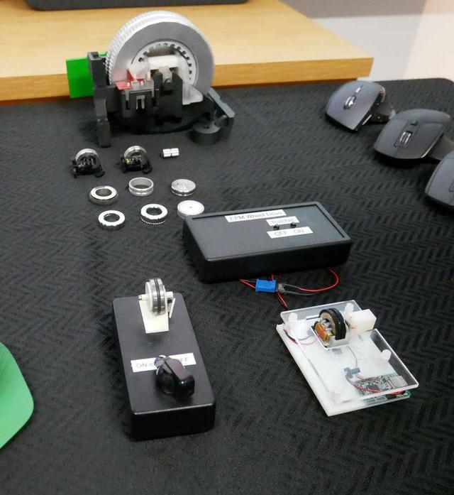 画像: 電磁ホイールの各種試作機。手前右が1号機。同左の箱状のものが2号機。奥にあるのが電磁ホイールの拡大模型