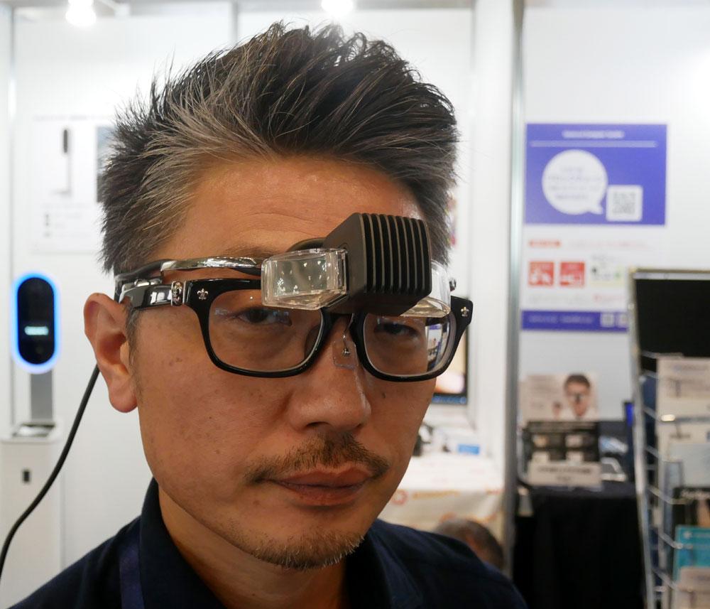 画像: ▲Enhanlaboブースでは、メガネスーパーのノウハウを投入したウエアラブルデバイス「b.g.」を展示(発売中)。オーバーグラスタイプ(眼鏡on眼鏡)で、両眼視、デバイスは有機EL、パネルは1280×720という仕様だ。グラス部分は移動させることができ、周囲を見ながら表示を見たり、使用しない時は上にはね上げておくことも可能だ。本体はモバイルバッテリーで駆動でき、HDMI入力に対応するので、スマホやタブレットからの動画再生も楽しめる