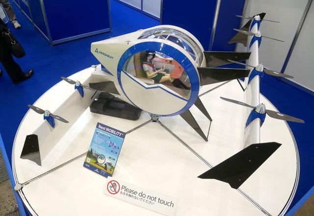画像: ▲エアロネクストでは、次世代の有人エアモビリティとなる「Next MOBILITY」を展示。1/3サイズで、ミニチュア試作機では実際に飛行も可能。キャビンはジャイロ付きで水平を保つ機構が内蔵されている。2025年の実用化を目指すという
