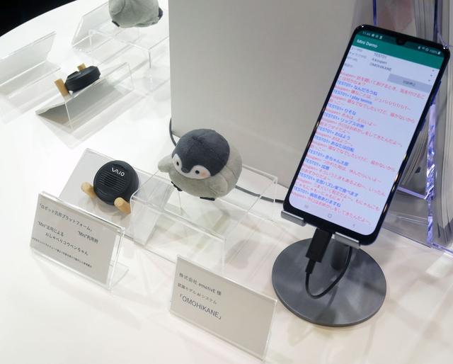 画像: ▲VAIOでは、パソコンの製造技術を使って各種ロボットの設計・製造も行なっているそう。写真は円形スピーカーに対話機能を搭載した「ロボット汎用プラットフォーム」。中央のペンギンには、左のスピーカーが組み込まれており、スマホからの操作で、あたかもペンギンと対話しているかのような雰囲気が味わえるという。他にも「ハロ」や「KIROBO mini」などもVAIOの設計・製造とか