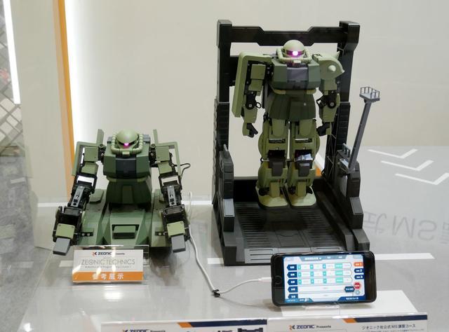 画像: ▲バンダイでは、ロボット開発会社のKONDOと提携して、自分でロボットを組み立てる「ZEONIC TECHNICS」を展開。これはパーツ状態のロボット(ザクIIね)を購入し、取説に従ってロボティスクを学びながら組み上げていくというもの。17個のモーターを制御してオリジナルのポーズ(動き=モーション)を取らせることもできるそう。そのモーションを組み合わせて、完成したロボットを操縦することも可能だ。来春発売で、価格は¥89,900+税。オプションでハンガーデッキやミニチュア作業員も用意されるそう