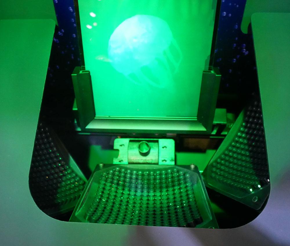 画像: ▲村田製作所では、ホログラムと疑似触覚(ハプティクス)を組み合わせた展示を実施。ホログラムが記録された材料(板)から浮かび上がって見える像=クラゲを触ろうとすると、下部に設置された超音波センサーによって、何もない空間(ホログラム映像に合わせて)に触覚を得られる、という仕組み