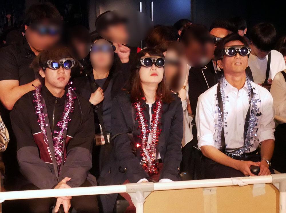画像: ▲座ってレイをかけている3人がデモに参加したファン