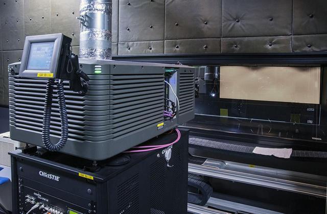 画像: ポストプロダクションセンター1内の試写室(写真上)。スクリーンサイズは横8.3m、縦3.5mというもので、クリスティの2Kプロジェクターで映像を投写している(写真左)。フロントL/C/Rに加え、12基のサラウンドスピーカーと3基のサブウーファーを備える