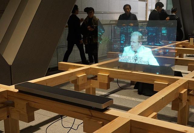 画像: 会場には木製のグリットがいくつも組まれており、様々なB&Oの製品がデモされていた。写真は透明スクリーンに投写した映像とBeosound Stageを組み合わせたもの