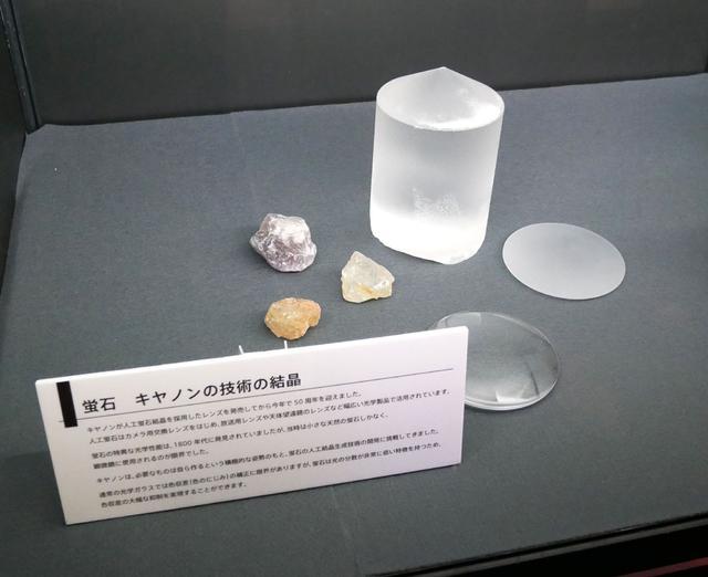 画像: ▲広報一押しが、蛍石レンズの展示。人工蛍石結晶採用レンズの発売から50周年ということで、あまり見ることのない大きな結晶(原石?)の展示も行なわれていた