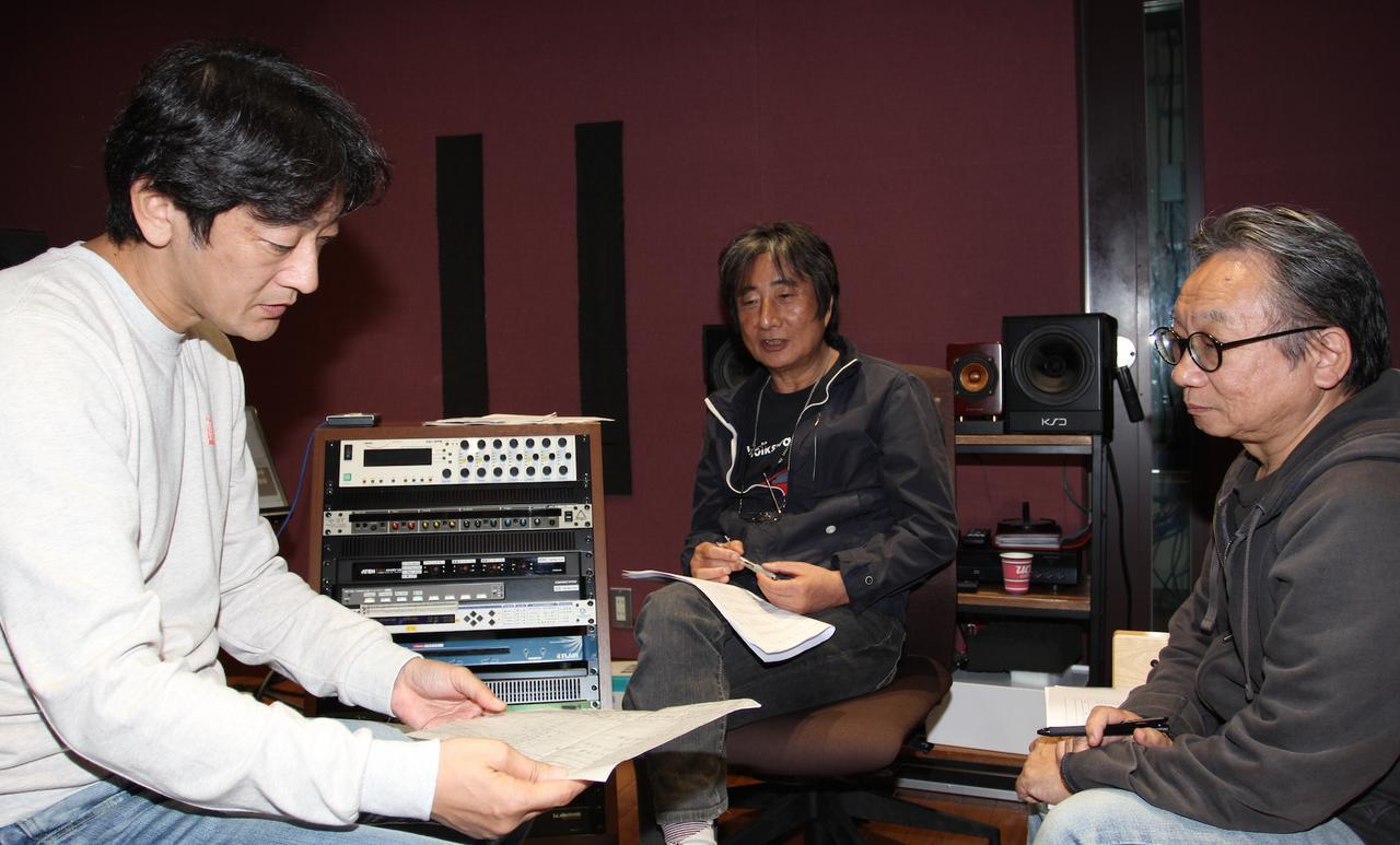 画像: 梅津氏(写真中央)は自らミックス・ダウンに携わったアナログ・マスターテープに約40年ぶりに接し、当時の記憶がまざまざと蘇ってくる……。筒美京平さんがひんぱんに通っていたスタジオ近くのレコード・ショップの話をふると、「竹下通りの『メロディ・ハウス』ですね」と、湯浅氏(写真右)が返す場面も