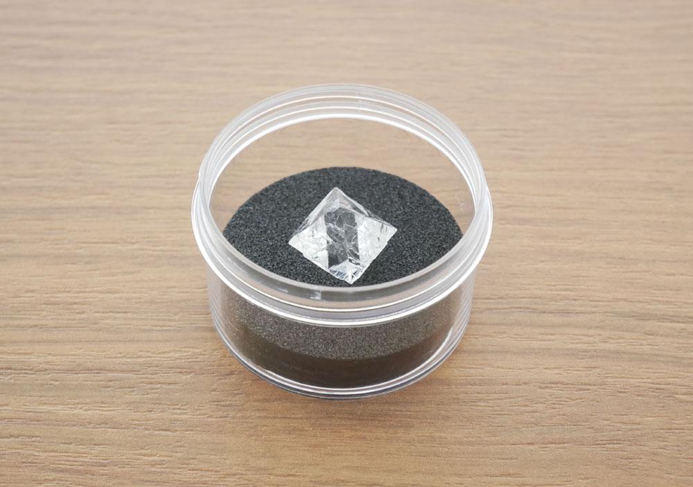 画像: プレゼントの「人工蛍石結晶の八面体ブロック」は、写真のケースに入れてお届けします。直接手で触るとけがをする可能性もあるので、取り扱いにはくれぐれもご注意下さい
