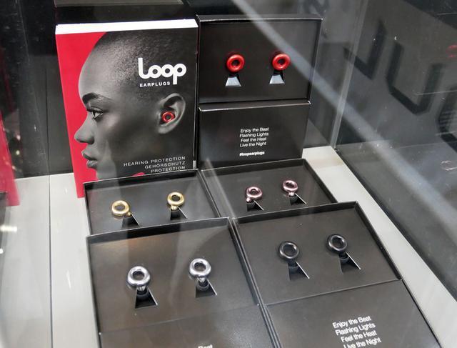 画像: ▲LOOPブランドのイヤープラグ(耳栓)。普通のイヤホンのように装着する。輪っかの部分に音を取り込む切り欠きがあり、そこから取り入れた音を約20dB音圧のみを下げて耳へ届けてくれるという