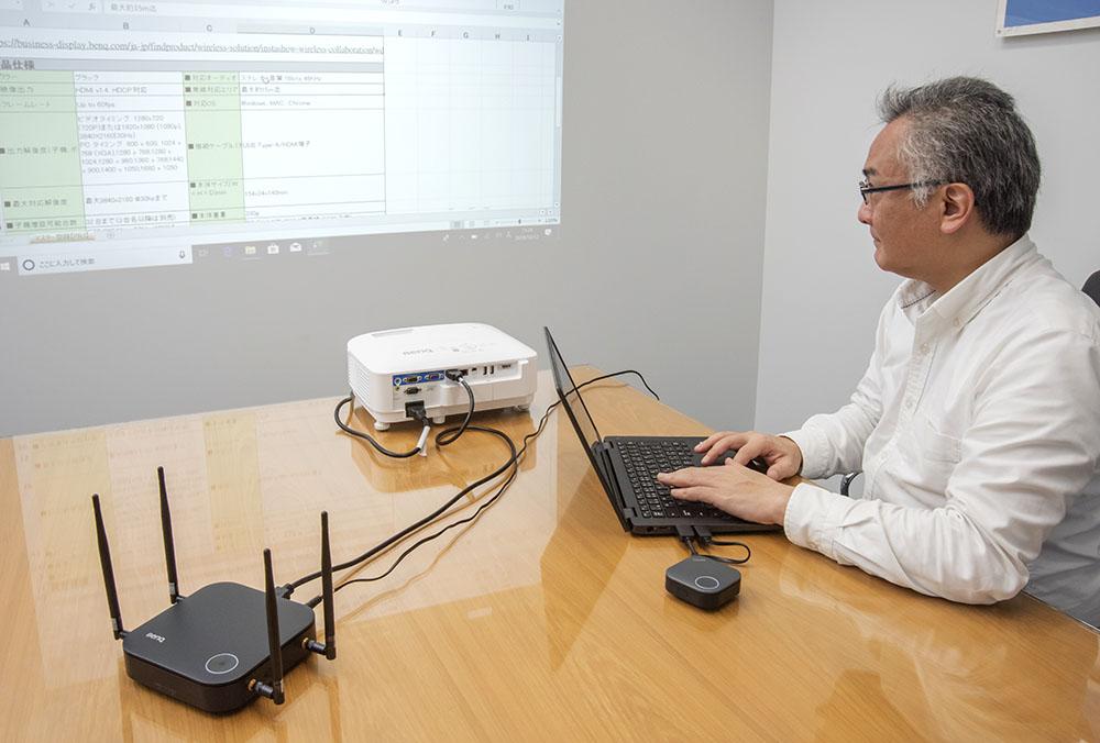画像: 実際にWDC20経由でノートパソコンをプロジェクターにつないだ状態で、鳥居さんにエクセルなどのビジネスアプリを操作してもらった。壁面投写だったが、文字もしっかり識別できてストレスはない。入力の切り替えの早さを考えると、会議の効率が格段によくなることは間違いないだろう