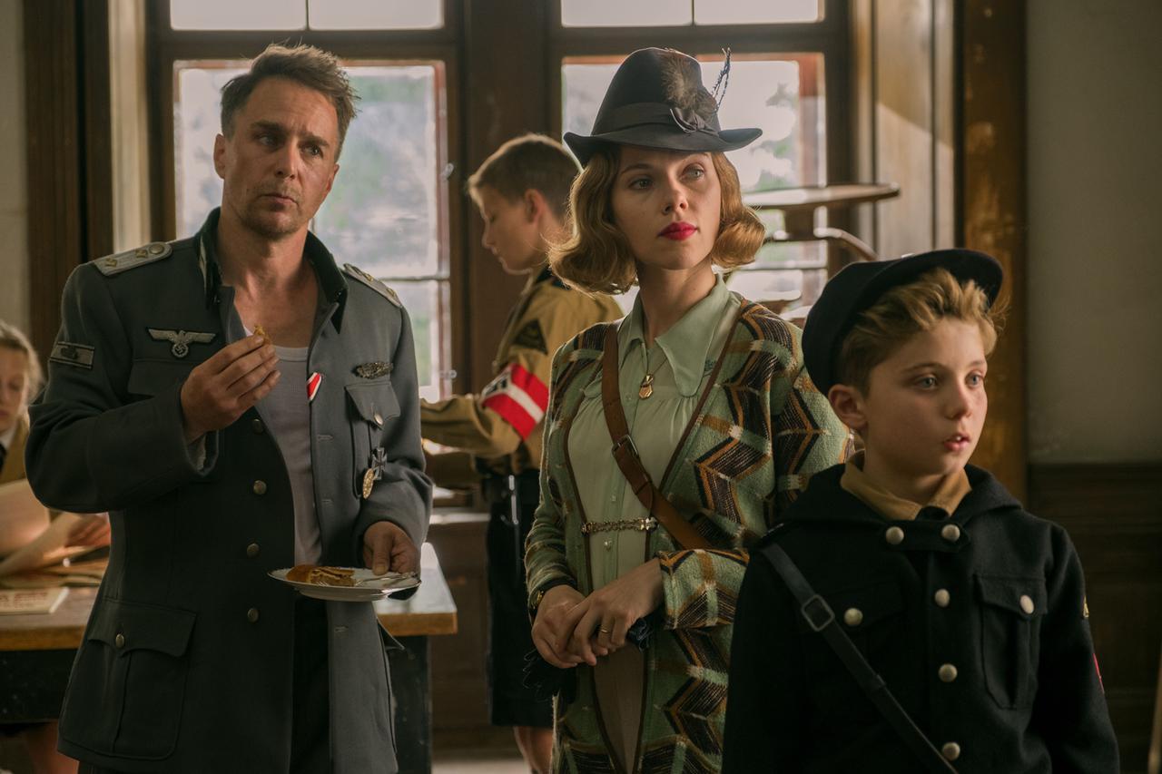 画像: 実は冷静に戦況を見ている酔っ払いのドイツ軍大尉(サム・ロックウェル/左)や、戦時下でも自由に明るく生きる美しい母親(スカーレット・ヨハンソン/中央)など、それぞれのキャラクターが立っている