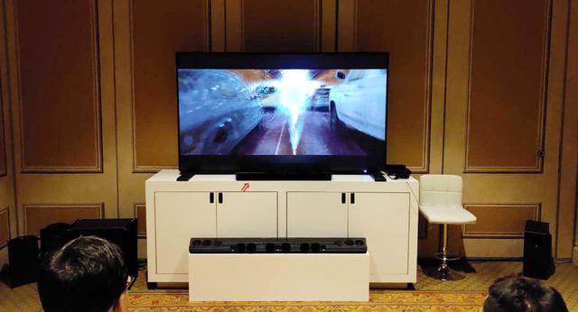 画像: TVの前に設置してあるのが「SXFI CARRIER」(赤い矢印)。一段低い位置にあるのは、日本では未発売のドルビーアトモス対応のサウンドバー。幅は約140cm