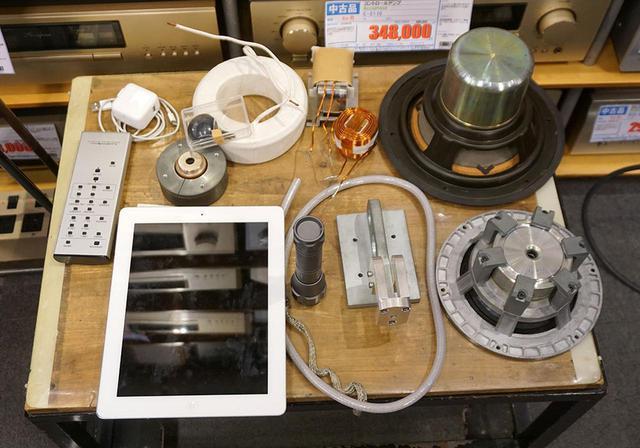 画像: DS-4NB70のパーツ(一部試作時の検討部品などもあり)。iPadの横、懐中電灯の右にあるのがトゥイーターユニットを固定するための金具とのこと