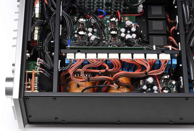 画像: 本機の最大の特徴はLECUTAと名付けられた電子制御トランス式アッテネーターの搭載。34タップのファインメット・コア・トランス(写真手前)と対を成す34個のリレー(写真のトランスの奥)を位置情報検出用ボリュウムノブ(左、フロントパネルに設置)で切り替えるという設計で、ボリュウム自体には音楽信号が流れない方式。