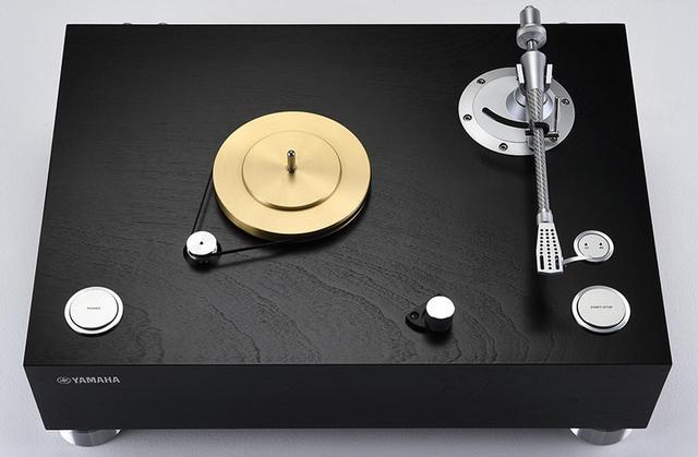 画像: ↑ヤマハGTシリーズ伝統の木質系素材によるキャビネットは、高密度パーティクルボード4層構造で単体重量14.3kg。ベルトドライブ型で、24極2相ACシンクロナスモーターにはクォーツ制御による正弦波を供給。プラッターはインナーが真鍮製、メインがアルミ製で共振点分散を図る。トーンアームの右がスタート/ストップと回転数の切り替えスイッチ。