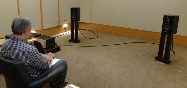 画像: ↑試聴する三浦氏。試聴室の標準ポジションにセッティングした。